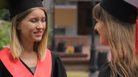 Two beautiful students in academic dresses and hats discussing future plans. Stock footage stock video footage