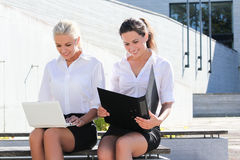 Two beautiful students sitting with laptop over street backgroun Stock Photography