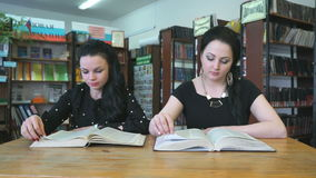Two beautiful students sitting at library stock footage
