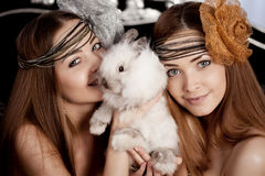 Two beautiful stylish girls with a rabbit Royalty Free Stock Photos