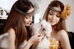 Two beautiful stylish girls with a rabbit Stock Image