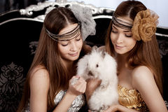 Two beautiful stylish womans with a rabbit Stock Image