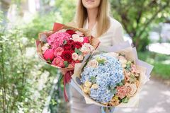 Two Beautiful summer bouquet. Arrangement with mix flowers. Young girl holding a flower arrangement with hydrangea. The. Beautiful summer bouquet. Arrangement royalty free stock photography