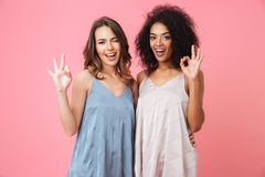 Two beautiful summer girls 20s with different color of skin in d. Resses smiling at camera and showing ok or alright sign isolated over pink background stock photo