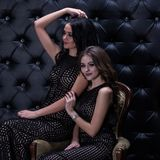 Two beautiful tanned girl models with dark hair sit on one armchair on a black background with rhinestones. Artistic photo. A squa stock images