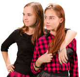 Two beautiful teen girls in red and black clothes. Standing on white background royalty free stock image