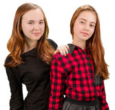 Two beautiful teen girls in red and black clothes. Standing on white background royalty free stock photos