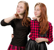 Two beautiful teen girls in red and black clothes. Standing on white background royalty free stock photo