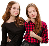 Two beautiful teen girls in red and black clothes. Standing on white background stock photos