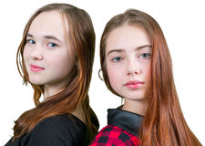 Two beautiful teen girls in red and black clothes. Standing on white background stock photo