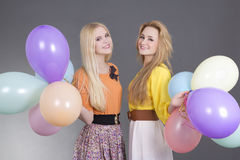 Two beautiful teenage girls with colorful balloons Stock Photos
