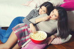 Two beautiful teenage girls eating popcorn and watching movies Royalty Free Stock Image
