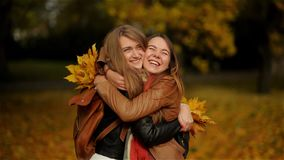 Two Beautiful Teenage Girls Hugging and Holding a Bouquet of Yellow Leaves in the Autumn Park, Girlfriends Having Fun in