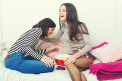 Two beautiful teenage girls laughing and gossiping at home Royalty Free Stock Image