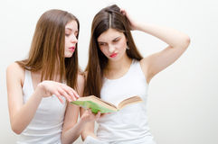 Two beautiful teenage girls reading book together Stock Photo