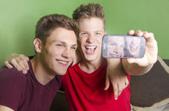 Two beautiful teenagers  taking a selfie. Two beautiful teenage brothers taking a selfie in their home, clean background Royalty Free Stock Photos