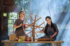 Two Beautiful Thai women smile in karen suit spinning thread on. A bamboo mat in a forest nature local village Thailand Stock Photography