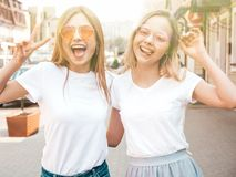 Two beautiful trendy girls posing in the street royalty free stock photos