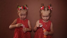 Two beautiful twin sisters in delightful red dresses blow soap bubbles together in the room of the house. Two beautiful twin sisters in delightful red dresses stock video