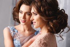 Two beautiful twins young women in luxury dresses, pastel colors. Beauty fashion portrait royalty free stock photo