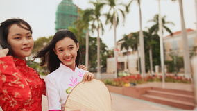 Two beautiful Vietnamese girl doing selfie with phone in national dresses Ao Dai. Shot in Full HD - 1920x1080, 30fps stock video