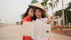 Two beautiful Vietnamese girl doing selfie with phone in national dresses Ao Dai. Shot in Full HD - 1920x1080, 30fps stock video footage