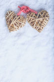 Two beautiful vintage entwined beige flaxen hearts tied together with a ribbon on white snow. Love and St. Valentines Day concept. Two beautiful romantic vintage Royalty Free Stock Images