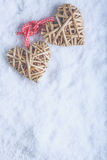 Two beautiful vintage entwined beige flaxen hearts tied together with a ribbon on white snow. Love and St. Valentines Day concept. Two beautiful romantic vintage Stock Photos