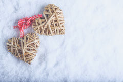 Two beautiful vintage entwined beige flaxen hearts tied together with a ribbon on white snow. Love and St. Valentines Day concept. Two beautiful romantic vintage Royalty Free Stock Photography