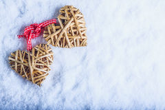 Two beautiful vintage entwined beige flaxen hearts tied together with a ribbon on white snow. Love and St. Valentines Day concept. Two beautiful romantic vintage Stock Image