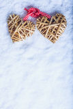 Two beautiful vintage entwined beige flaxen hearts tied together with a ribbon on white snow. Love and St. Valentines Day concept Royalty Free Stock Photos