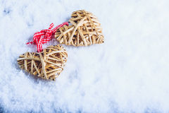 Two beautiful vintage entwined beige flaxen hearts tied together with a ribbon on white snow. Love and St. Valentines Day concept. Two beautiful romantic vintage Stock Photo
