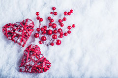 Two beautiful vintage red hearts with mistletoe berries on a white snow background. Christmas, love and St. Valentines Day concept Royalty Free Stock Photos