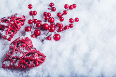 Two beautiful vintage red hearts with mistletoe berries on a white snow background. Christmas, love and St. Valentines Day concept Stock Photos