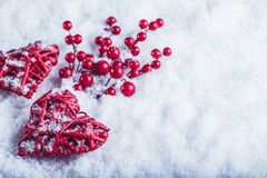Two beautiful vintage red hearts with mistletoe berries on a white snow background. Christmas, love and St. Valentines Day concept Royalty Free Stock Images