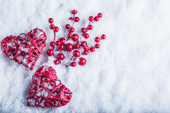 Two beautiful vintage red hearts with mistletoe berries on a white snow background. Christmas, love and St. Valentines Day concept Royalty Free Stock Photography