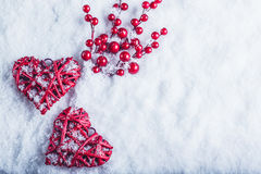Two beautiful vintage red hearts with mistletoe berries on a white snow background. Christmas, love and St. Valentines Day concept Stock Photography