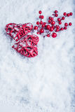 Two beautiful vintage red hearts with mistletoe berries on a white snow background. Christmas, love and St. Valentines Day concept Stock Image