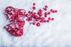 Two beautiful vintage red hearts with mistletoe berries on a white snow background. Christmas, love and St. Valentines Day concept Royalty Free Stock Photo