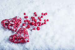 Two beautiful vintage red hearts with mistletoe berries on a white snow background. Christmas, love and St. Valentines Day concept Stock Photo