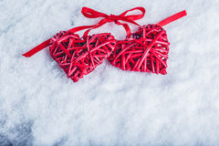 Two beautiful vintage red hearts tied together with a ribbon on a white snow background. Love and St. Valentines Day concept. Royalty Free Stock Images