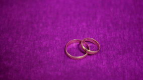 Two beautiful wedding ring on a dark purple background.  stock video footage