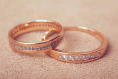 Two beautiful wedding rings with brilliants close up, vintage toned Royalty Free Stock Images