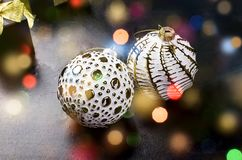 Elegant Christmas background with white retro balls and gifts. Two beautiful white and golden christmas balls and black gift box with gold ribbon on a black stock photography