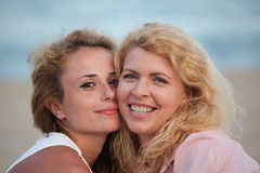 Two beautiful woman best friends on beach having fun Stock Photo
