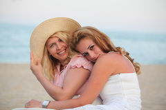 Two beautiful woman best friends on beach having fun Stock Image