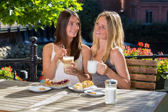 Two beautiful woman friends in outdoor cafe. Two beautiful women friends sitting close in outdoor cafe drinking coffee, chatting and smiling, enjoying desserts Royalty Free Stock Photography