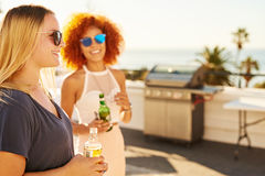 Two beautiful woman holding drinks with smiles on their faces. Two beautiful women holding alcoholic ciders with smiles on their faces while standing on a Stock Image