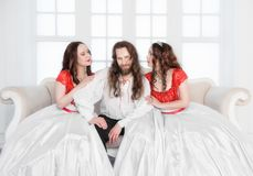 Two beautiful woman and man in medieval costumes royalty free stock photography