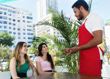 Two beautiful woman place an order at a caucasian waitress Royalty Free Stock Images